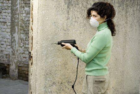 Femme portant un masque à l'aide d'une ponceuse électrique. Horizontalement photo encadrée. Banque d'images - 3526582