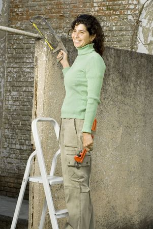 Smiling woman holding a saw and standing on a ladder. Vertically framed photo. photo