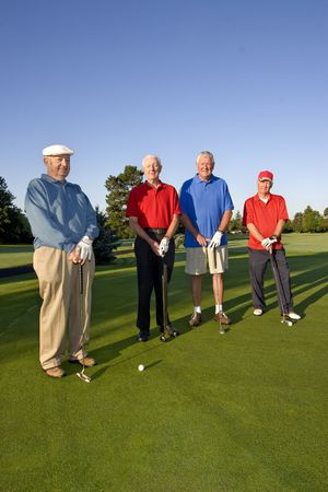 Four elderly men are standing together on a golf course. They are holding their clubs, smiling, and looking at the camera.  Vertically framed shot. Imagens
