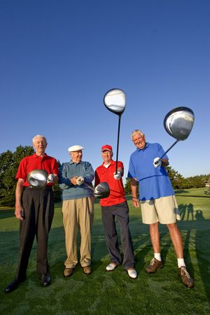 Four elderly men are standing together on a golf course. They are holding their clubs, smiling, and looking at the camera.  Vertically framed shot. Stockfoto