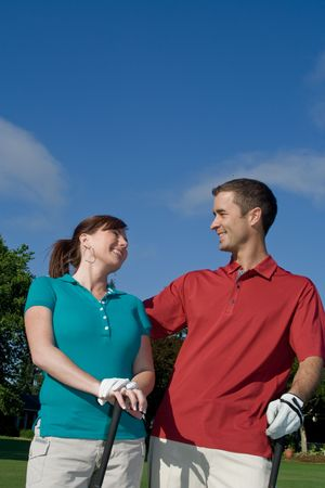 vertically: Golfers stand in front of camera. They are leaning back and smiling at eachother. Vertically framed photo.