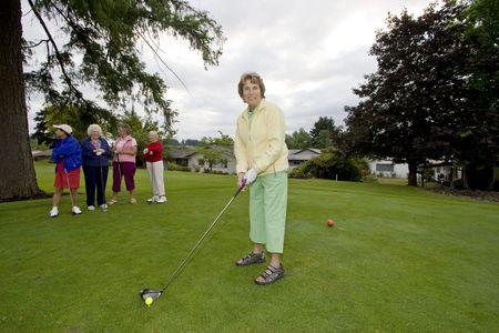 Five elderly women playing golf photo