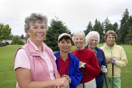 Cinq souriant, les femmes âgées transportant des clubs de golf. Horizontalement photo encadrée. Banque d'images