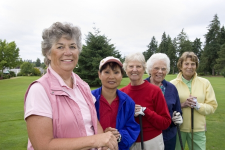 Five smiling, elderly women carrying golf clubs. Horizontally framed photo.