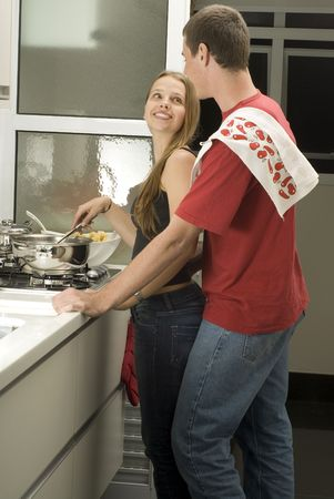 vertically: Man and woman stand in kitchen smiling at eachother. Woman stirs while man stands behind her. Vertically framed photo.