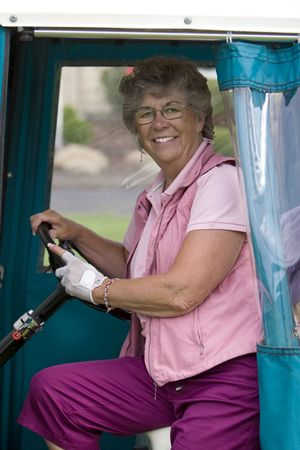 vertically: Elderly woman with golf glove smiling as she rides in a golf cart. Vertically framed photo. Stock Photo