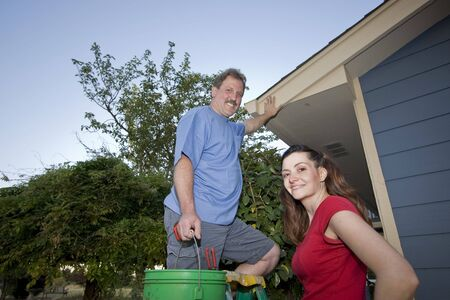 Man and woman standing on a ladder near a blue house. Horizontally framed shot. photo