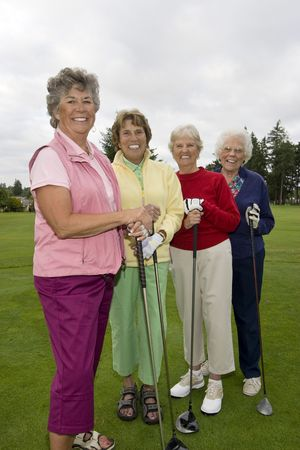 Four smiling, elderly women carrying golf clubs. Vertically framed photo. photo