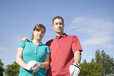 sternly: A young couple is standing on a  course.  The man has his arm around the woman and they are looking sternly at the camera.  Horizontally framed shot.