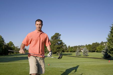 sternly: A man is standing on a golf course.  He is holding a golf club and is looking sternly at the camera.  Horizontally framed shot. Stock Photo