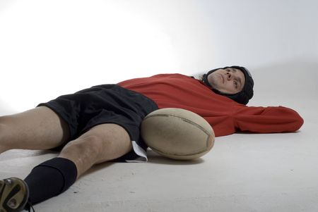 Rugby player lays on the floor with his football.  Horizontally framed photograph