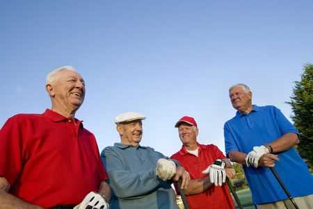 Four elderly men are standing together on a golf course. They are holding their clubs, smiling, and looking away from the camera.  Horizontally framed shot.