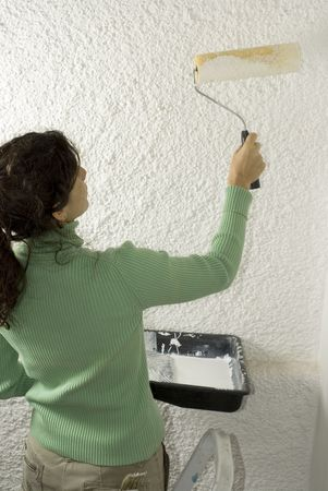 vertically: Woman uses a paint roller to paint a wall. Vertically framed photo. Stock Photo