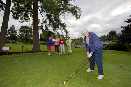 Five elderly women playing golf
