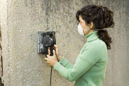 Femme portant un masque de peinture utilize une ponceuse électrique à un mur de sable. Horizontalement photo encadrée.  Banque d'images - 3526779