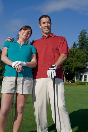 vertically: Golfers stand in front of camera. Man has arm around woman and they are laughing at camera. Vertically framed photo. Stock Photo