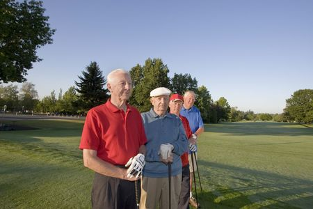 Four elderly men are standing together on a golf course. They are holding their clubs, and some are smiling at the camera.  Horizontally framed shot. photo