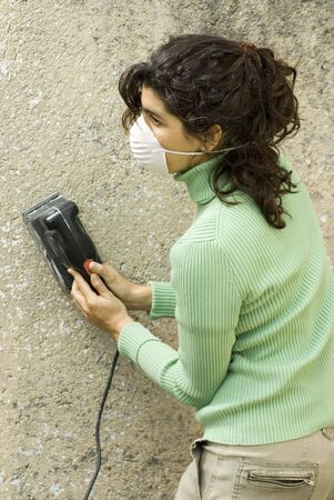 Woman holds electric sander while wearing mask. Vertically framed photo.