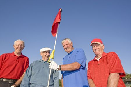 Four elderly men are standing on a golf course.  They are smiling and looking at the camera and one man is holding a flag.  Horizontally framed shot.