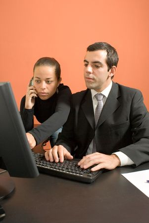 Businessman and woman hover over a computer Stock Photo