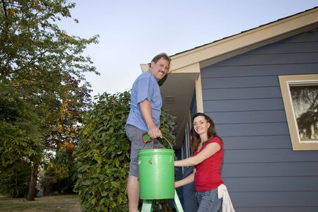 Man and woman standing on a ladder near a blue house. They are smiling at the camera. Horizontally framed shot. photo