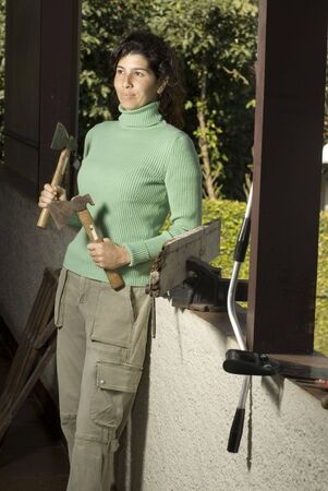 Smiling woman leans against a wall holding two hatchets. Vertically framed photo. Stock Photo - 3526081