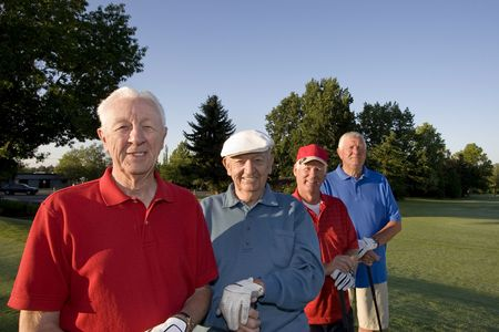 Four elderly men are standing together on a golf course. They are holding their clubs, smiling, and looking at the camera.  Horizontally framed shot.