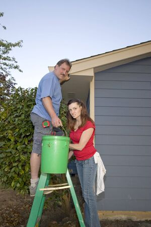 Man and woman standing on a ladder near a blue house. Vertically framed shot. photo