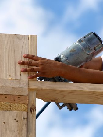 Hand holding a piece of wood and drilling it.