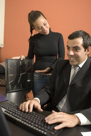 Businessman typing as his secretary looks on. Vertically framed photo.