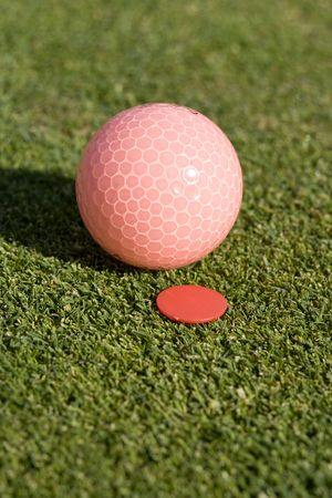 A golf ball is sitting on the green of a golf course right next to a marker.  Vertically framed shot. photo