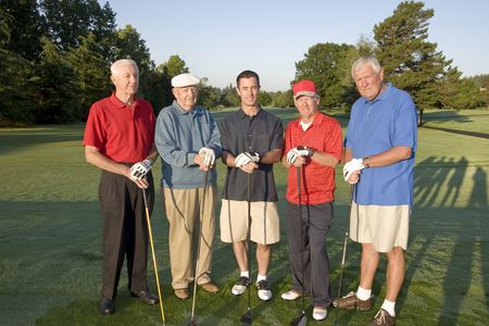 A group of four elderly men and one younger man is standing together on a golf course. They are holding their clubs, smiling, and looking at the camera.  Horizontally framed shot. photo
