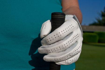 골퍼의 낀 손으로 골프 클럽을 보유하고 있습니다. 가로로 액자 사진입니다.