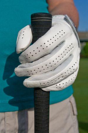 골퍼의 낀 손으로 골프 클럽을 보유하고 있습니다. 세로 액자 사진입니다. 스톡 콘텐츠