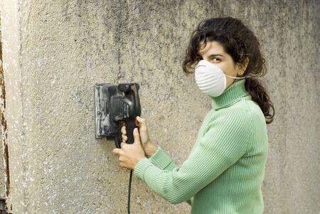 Femme portant un masque à l'aide d'une ponceuse électrique. Horizontalement photo encadrée. Banque d'images - 3526778