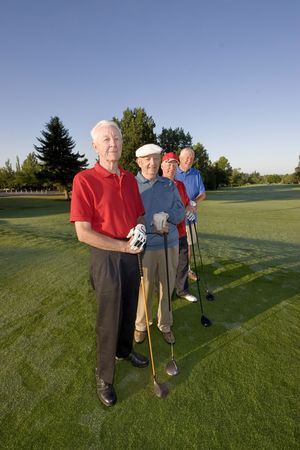 Four elderly men are standing together on a golf course. They are holding their clubs, smiling, and looking at the camera.  Vertically framed shot. photo