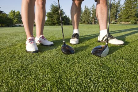 A man and a woman are standing on a golf course.  You can only see their legs and their clubs.  Horizontally framed shot.