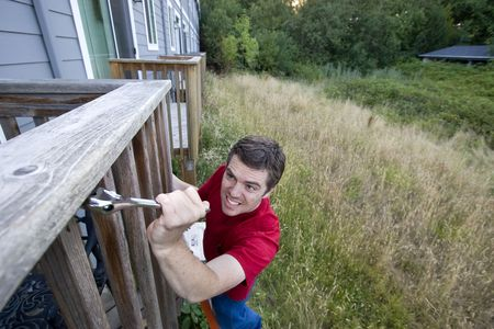 Man with a  grimace on his face standing on a ladder fixing a porch with a wrench. Horizontally framed photo. photo