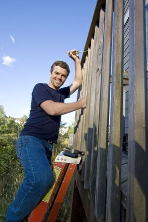 Happy man on a ladder repairing siding of a house with a screwdriver. Vertically framed photo. photo