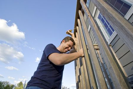 sufficient: Frowning man fixing the siding on a house with a screwdriver. Horizontally framed photo. Stock Photo