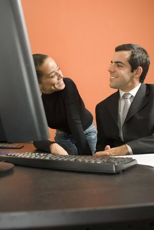 vertically: Businessman and woman looking at each other and smiling. They are in front of a computer. Vertically framed photo. Stock Photo