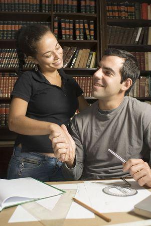 hombre sentado: Sentados hombre sacude parte de la mujer de pie. Ellos est�n estudiando y sonriente en s�. Foto enmarcada verticalmente.