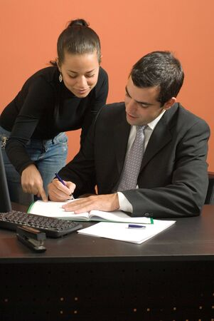Businessman sits at desk working on paperwork with a businesswoman who stands by him. Vertically framed photo. Stock Photo