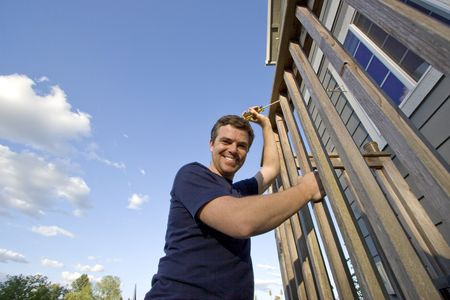 Smiling man fixing the siding on a house with a screwdriver. Horizontally framed photo. Stock Photo