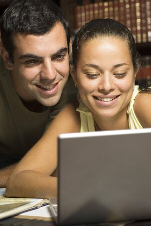 vertically: Man looks over womans shoulder. They are looking at her laptop. Vertically framed photo. Stock Photo