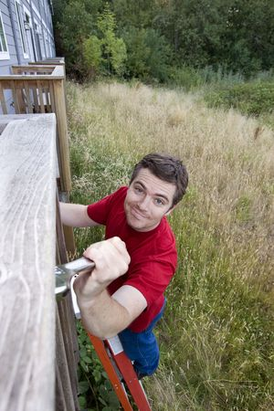 Man with a silly smile on his face standing on a ladder fixing a porch with a wrench. Vertically framed photo. photo