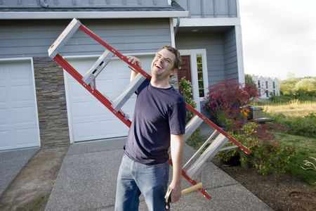 Laughing man standing in front of house holding ladder and hammer. Horizontally framed photo. Stock Photo