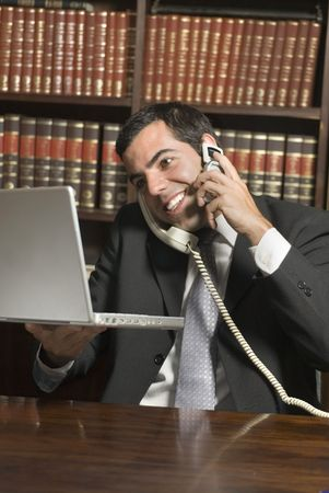 vertically: Smiling man in suit talks on two phones while holding laptop. Vertically framed photo.