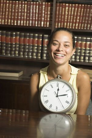 vertically: Woman smiles while holding a clock in front of her while seated at a table in a library. Vertically framed photo. Stock Photo
