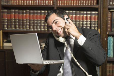Businessman on cell phone in office holding computer. Horizontally framed photo. Фото со стока